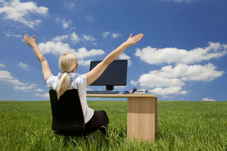 location shot: Business concept shot of a beautiful young woman sitting at a desk using a computer in a green field raising her arms into a bright blue sky with fluffy white clouds. Shot on location with copyspace at the top of the image.
