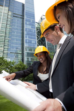 A group of three executives, one man and two women, wearing hard hats review architectural plans in a modern city environment. Stock Photo - 4963723