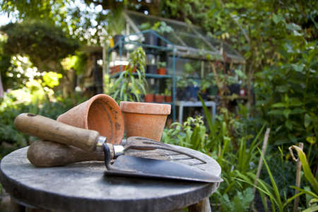 garden tools: Gardening utensils and flower pots resting on a stool in a green garden with a greenhouse out of focus in the background Stock Photo