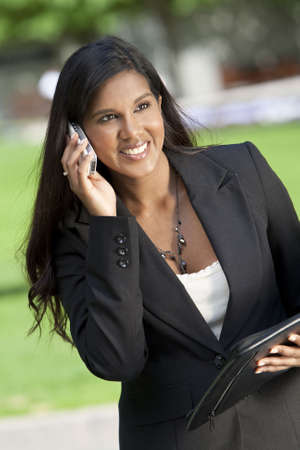 A beautiful young Asian businesswoman with a wonderful smile chatting on her cell phone Stock Photo - 4977440