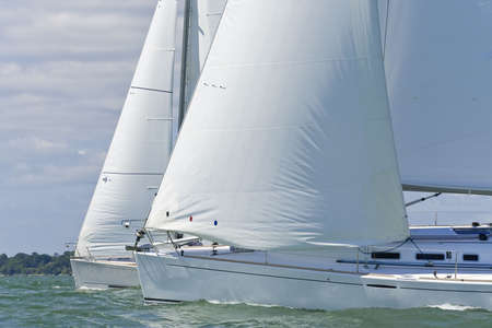 Two beautiful white yachts sailing close to each other on a bright sunny day photo