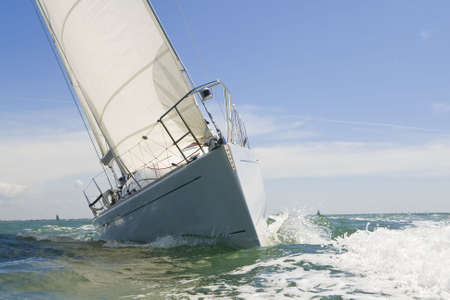 wind up: A beautiful white yachts racing close to the camera on a bright sunny day Stock Photo