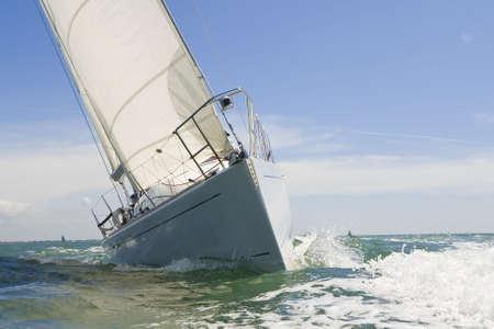 yacht race: Un hermoso blanco yates de carreras cerca de la c�mara en un brillante d�a soleado