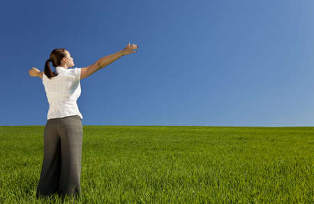 worship praise: A beautiful young woman holding her arms out in praise or celebration standing in a green field and facing towards the light in a blue sky Stock Photo