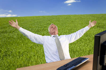 Business concept shot showing an older male executive using a computer in a green field with a blue sky complete with fluffy white clouds. Shot on location not in a studio. photo