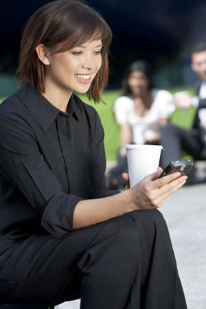 A beautiful young Eurasian woman with a wonderful smile texting on her cell phone while drinking coffee  photo