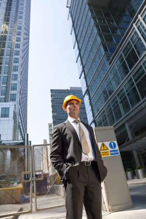 costruction: Shot showing a man dressed in a suit and hard hat on a costruction site in a modern city environment.  Stock Photo