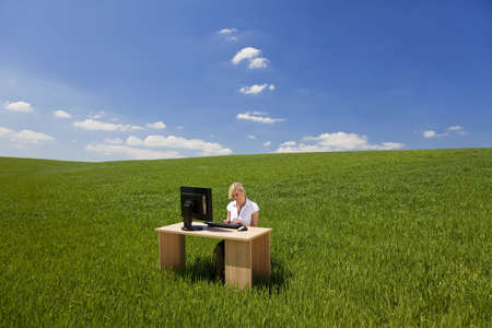 Business concept shot of a beautiful young woman sitting at a desk using a computer in a green field raising her arms into a bright blue sky with fluffy white clouds. Shot on location with copyspace at the top of the image. photo