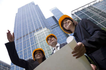 executive helmet: A group of three executives, one man and two women, wearing hard hats review architectural plans in a modern city environment.