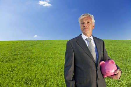 location shot: Investment concept shot of a senior man holding a big pink piggy bank in a green field with a bright blue sky. Shot on location not montaged.
