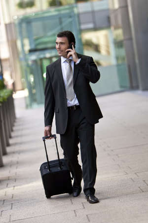 location shot: Successful businessman traveling with his suitcase and talking on his cell phone. Shot on location in a city or airport setting.