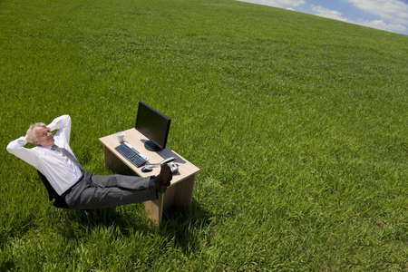 silver surfer: Business concept shot showing an older male executive relaxing at his desk in a green field with a blue sky. Shot on location not in a studio.