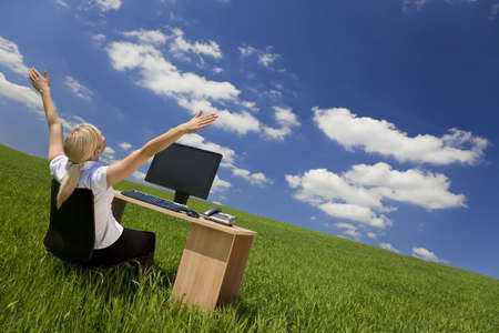 Business concept shot of a beautiful young woman sitting at a desk using a computer in a green field raising her arms into a bright blue sky with fluffy white clouds. Shot on location with copyspace at the top of the image.