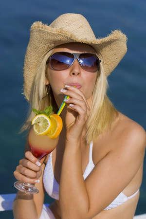 cappello cowboy: Sorprendente bellezza di giovane donna bionda in paglia cappello da cowboy e occhiali da sole godendo un cocktail da un mare blu profondo Archivio Fotografico