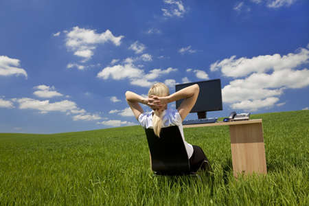 location shot: Business concept shot of a beautiful young woman relaxing at a desk in a green field with a bright blue sky. Shot on location.