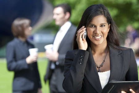 indian summer: A beautiful young Asian businesswoman with a wonderful smile shot using her cell phone outside with her colleagues out of focus behind her. Stock Photo