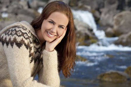 knitwear: A beautiful Scandinavian woman wearing traditionally patterned knitwear sitting and relaxing by a flowing mountain stream