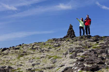location shot: A man and a woman at the top of a mountain standing next to a cairn, the woman is pointiing to a distant horizon. Traditionally these rock piles were signposts but in recent times adding stones to them is deemed to bring good luck. Shot on location in Ice Stock Photo