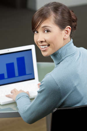 toothy: A beautiful young oriental woman with a wonderful toothy smile using a laptop in her office