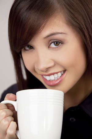 toothy: A beautiful young oriental woman with a wonderful toothy smile drinking from a white mug Stock Photo