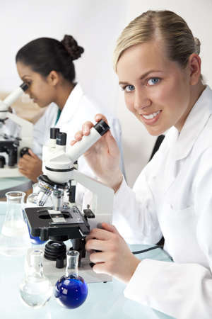 A blond female medical or scientific researcher or doctor using her microscope in a laboratory with her Asian colleague out of focus behind her. photo