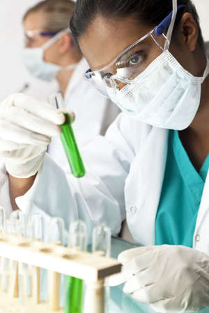An Asian medical or scientific researcher or doctor using looking at a green solution in a laboratory with her female colleague out of focus behind her. photo