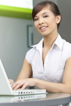 A beautiful young oriental woman with a wonderful toothy smile using a laptop  photo