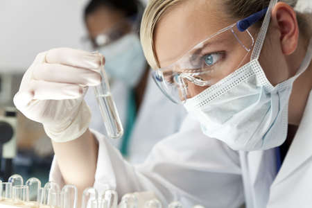 scientific: A blond medical or scientific researcher or doctor using looking at a clear solution in a laboratory with her Asian female colleague out of focus behind her.