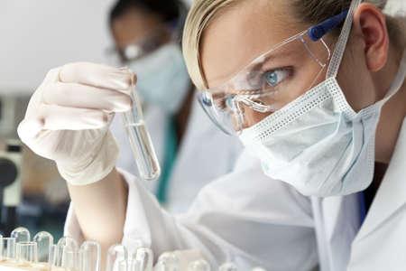 Un chercheur blonde médicale ou scientifique ou médecin à l'aide à la recherche d'une solution claire dans un laboratoire avec son collègue d'Asie hors foyer derrière elle.