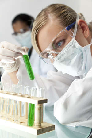 A blond medical or scientific researcher or doctor using looking at a green solution in a laboratory with her Asian female colleague out of focus behind her. Stock Photo