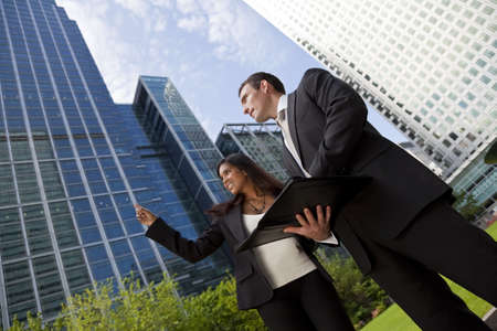 person outside: A smiling businesswoman and her male colleague taking part in a happy business meeting outside in a modern city environment