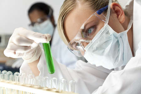 A female medical or scientific researcher or doctor looking at a green solution in a laboratory with her Asian female colleague out of focus behind her. Stock Photo - 5463173