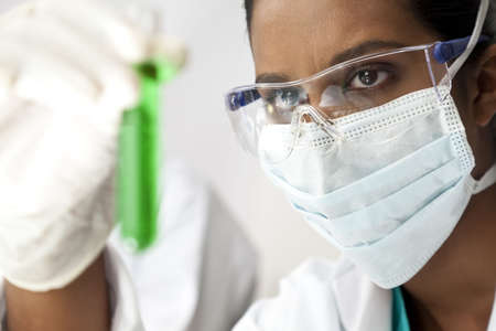 An Asian medical or scientific researcher or doctor looking at a test tube of green solution in a laboratory. photo