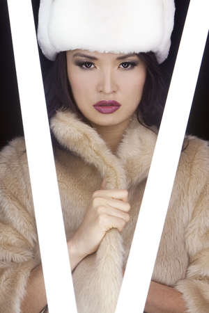 A stunningly beautiful young Japanese Asian woman illuminated by glowing fluorescent tubes and wearing (fake) fur hat and coat photo