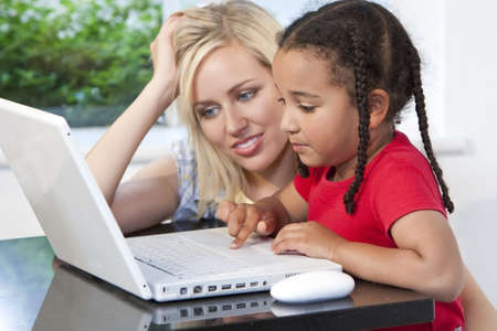 home schooling: A beautiful young mother and her mixed race young daughter using a laptop at home in the kitchen.