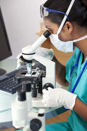 Un asi�tico m�dico femenino o investigador cient�fico utilizando su microscopio en un laboratorio.