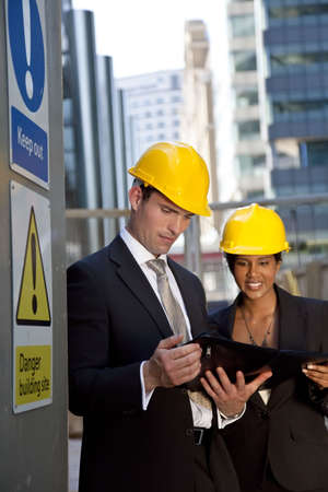 A male manager on a construction site wearing a hard hat and talking with his Asian female colleague photo