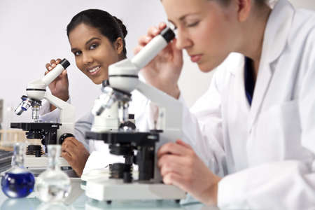 clinical research: An Asian female medical or scientific researcher or doctor using her microscope in a laboratory with her colleague out of focus in the foreground. Stock Photo