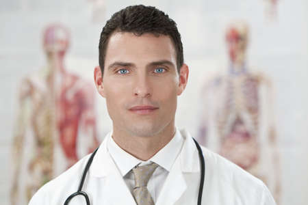 bata blanca: Un doctor con una bata blanca con estetoscopio de pie delante de gr�ficos de la anatom�a humana. Foto de archivo