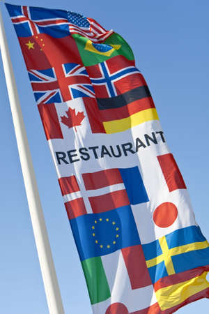 commercially: A generic restaurant sign with the flags of many nations on it. This is not specific to any particular restaurant but is commercially available and not subject to copyright. The various national flags are listed in the keywords. Stock Photo