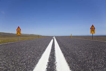 warning signs: A ground level shot of a wide open road with warning signs