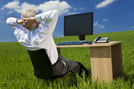 silver surfer: Business concept shot showing an older male executive relaxing at his desk with a computer in a green field with a blue sky complete with fluffy white clouds. Shot on location not in a studio.