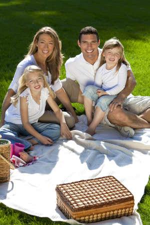 Una joven familia con el padre de la madre y dos hijas rubias con un picnic en un parque verde ba�ada por el sol