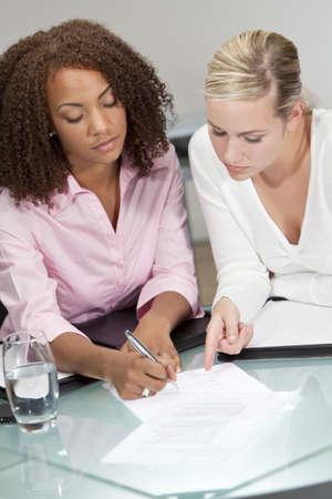 signing: Due belle giovani donne d'affari o avvocati, uno African American uno caucasico, la discussione e la firma di un contratto o documento legale