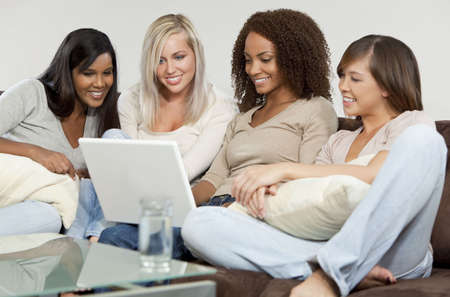 all one: Four mixed race girls, one African American, one Indian, one Asian and one caucasian all having fun using a white laptop computer Stock Photo