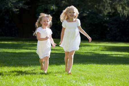Two pretty young blond girls wearing white dresses and having fun running through a green park in summer sunshine