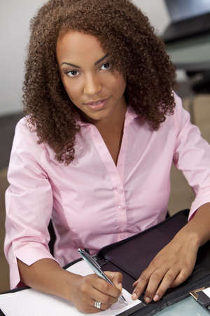 A beautiful mixed race African American girl, student or businesswoman sitting at a desk and writing. Stock Photo - 5654448
