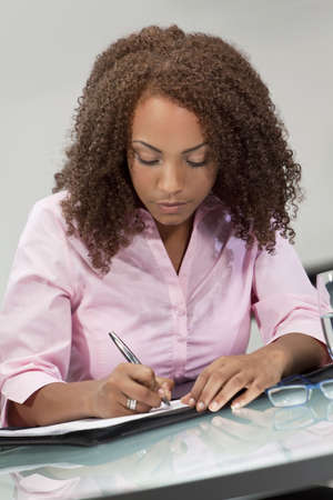 A beautiful mixed race African American girl, student or businesswoman sitting at a desk and writing. Stock Photo - 5654449