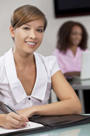 A beautiful young Chinese oriental Asian woman working in an office with her African American colleague out of focus behind her. Stock Photo - 5654446