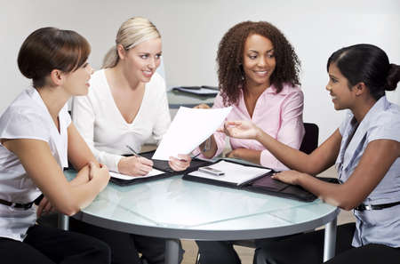 one to one meeting: Four women having a business meeting in an office, one African American, one Chinese Asian, One Indian Asian and one Caucasian